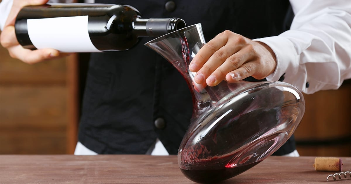waiter decanting a bottle of wine